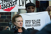"""Supporters of Mark Duggan's family hold a vigil outside Tottenham  police station. They gathered, alongside family members and his mother Pam Duggan and Aunt Carole Duggan (pictured) , at 2pm following an inquest jury ruling that Duggan was lawfully killed when police shot him dead while he was unarmed.  Within days of his shooting, in 2011, rioting broke out on the streets of London, and spread to other urban areas in England.  Pastor Nims Obunge, who oversaw Duggan's funeral in 2011, said: """"The message from the family is that this vigil is intended to be a very peaceful vigil"""". Tottenham, London, UK 11 January 2014. Guy Bell, 07771 786236, guy@gbphotos.com"""