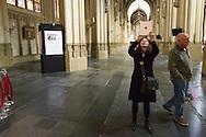 Nederland, Den Bosch, 20160409<br /> Vrouw, toeriste, houdt een iPad omhoog om een foto te maken in de kerk.<br /> Kathedraal St. Jan in Den Bosch.De Sint-Janskathedraal (voluit: de Kathedrale Basiliek van Sint-Jan Evangelist) in de binnenstad van 's-Hertogenbosch wordt veelal beschouwd als het hoogtepunt van de Brabantse gotiek. De kathedraal imponeert door zijn omvang en enorme rijkdom aan beeldhouwwerk. Uniek in Nederland zijn de dubbele luchtbogen en uniek in de wereld zijn de 96 luchtboogfiguren.De kerk in volle pracht op de Parade<br /> Sint-Janskathedraal<br /> <br /> Netherlands, Den Bosch<br /> The St. John's Cathedral (in full: the Cathedral Basilica of St. John the Evangelist) in the city of 's-Hertogenbosch is often regarded as the pinnacle of Brabant Gothic. The cathedral impresses by its size and wealth of sculpture. Unique in the Netherlands are the double flying buttresses and unique in the world, the 96 flying buttress figures.<br /> St. John's Cathedral