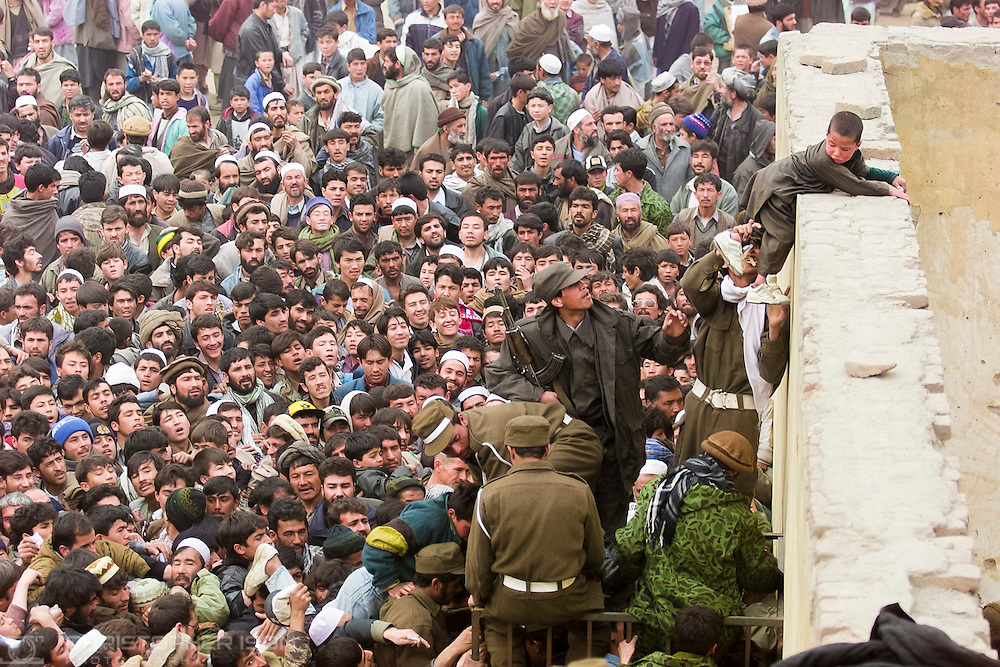 Afghan men attempt to enter the Olympic Stadium in Kabul to watch a football match between Kabul FC and a British Military XI. Chaos was caused when it became clear that hundreds of fake tickets had been printed.