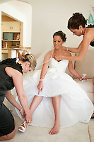 The bride tell a bridesmaid how her shoes gets laced.