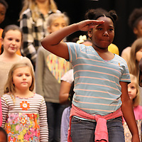 Lawhon Elementary School third grader Zkhariyona Garmon saluts the flag during the National anthem as they go through one last practice for their vetereans program Wednesday.