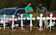 Two men stand at a row of memorial crosses near the site of the shooting at the First Baptist Church of Sutherland Springs, Texas, U.S., November 7, 2017.  REUTERS/Rick Wilking
