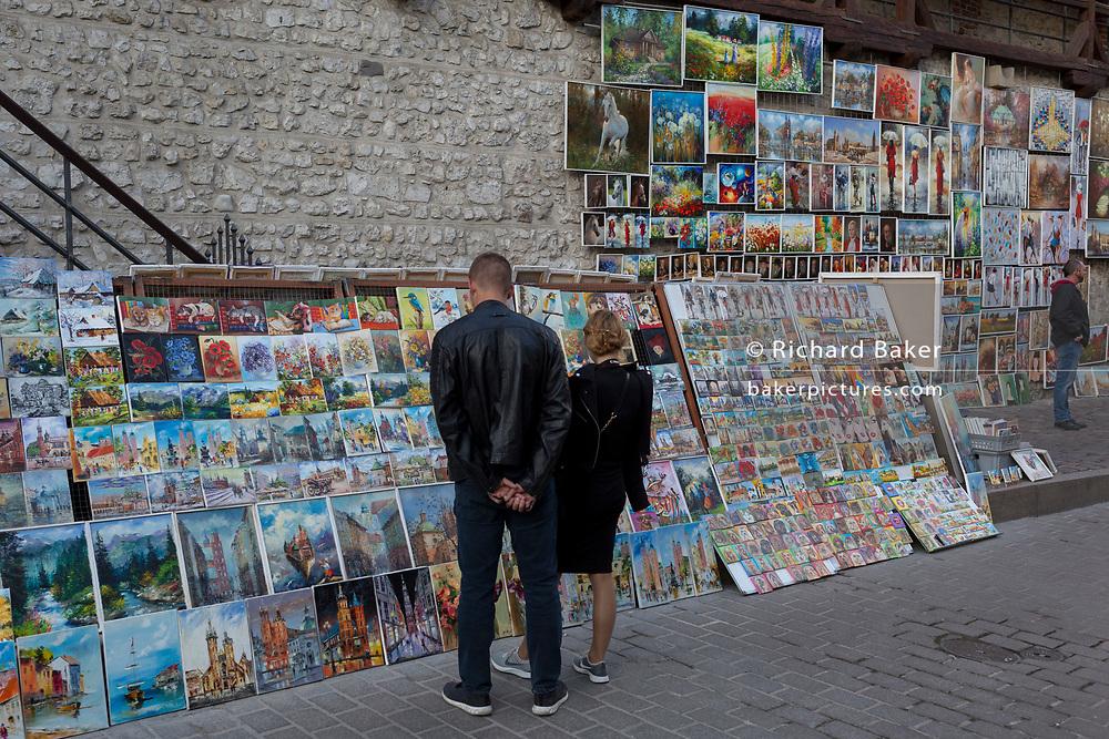 Tourist art is on display along Zanlek Ksiazat Czartoryskich, beneath the reconstituted city walls of the Florian Gate, on 22nd September 2019, in Krakow, Malopolska, Poland.