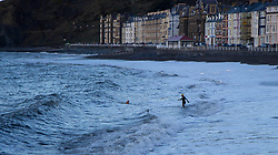 © Licensed to London News Pictures. 26/12/2013. A group of hardy people take advantage of the lull before the storm to go for a swim in the sea off Aberystwyth on Boxing Day. Photo credit : Jon Freeman/LNP