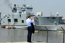 © Licensed to London News Pictures. 25/07/2012. London, UK .  A man takes a picture of HMS Ocean moored in the Thames for the Olympic games 2012 in the sunshine as temperatures reach 30 degrees at Greenwhich Pier in London today 25 July 2012. Photo credit : Stephen Simpson/LNP
