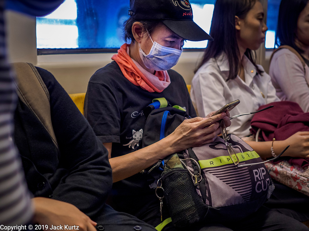 """14 JANUARY 2019 - BANGKOK, THAILAND:    A woman wearing a dust filter on the skytrain in Bangkok. Bangkok has been blanketed by heavily polluted air for almost a week. Monday morning, the AQI (Air Quality Index) for Bangkok  was 182, worse than New Delhi, Jakarta, or Beijing. The Saphan Kwai neighborhood of Bangkok recorded an AQI of 370 and the Lat Yao neighborhood recorded an AQI of 403. An AQI above 50 is considered unsafe. Public health officials have warned people to avoid """"unnecessary"""" outdoor activities and wear breathing masks to filter out the dust.    PHOTO BY JACK KURTZ"""