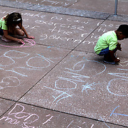 "Children use chalk to scribble messages as other activists take part in a rally on the steps of city hall in downtown Orlando, Florida on Saturday, May 5, 2013. The protesters gathered to support a global protest named  ""March Against Monsanto,"" demanding a stop to the use of agrochemicals and the production of genetically modified food, which according to them has harmful health effects, causing cancer, infertility and other diseases. Marches and rallies against seed giant Monsanto were held across the U.S. and in dozens of other countries. (AP Photo/Alex Menendez)"