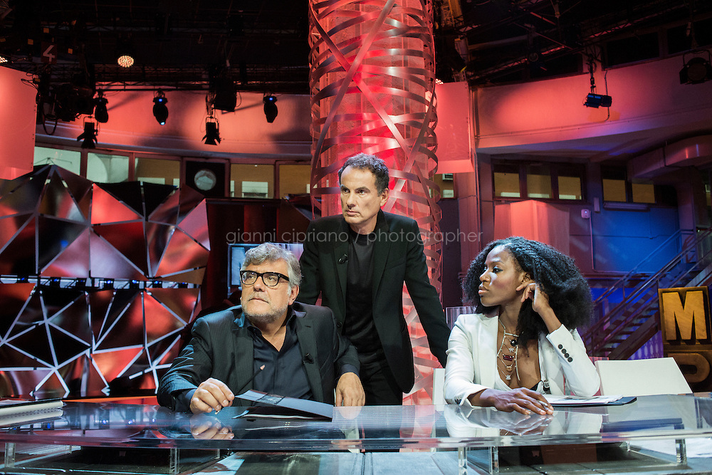 TURIN, ITALY - 23 October 2013: (L-R) Jurors of talent show Masterpiece Giancarlo De Cataldo (57), Andrea De Carlo (61) and Taiye Selasi (34) listen to the authors of the show before recording the first episode in the studios of RAI, the national Italian TV, in Turin, Italy, on October 23rd 2013.<br /> <br /> Masterpiece is the first talent show for aspiring writers, produced by Rai and FremantleMedia.  The show's objective is to find new talents in Italian literature. 4,919 manuscripts were sent to the program and 80 have been selected for the final selections that will be broadcasted from the Masterpiece studio at the RAI headquarters of Turin starting November 17th on Rai3 national TV. The winner will have his novel co-distributed by RCS and Bompiani, two Italian publishers. <br /> <br /> The jury is composed of Andrea De Carlo (a Milan based author of 17 novels among which is &quot;Due di due&quot;), Giancarlo De Cataldo (magistrate, screenwriter and author of &quot;Romanzo Criminale&quot;) and Taiye Selasi, author of TBK.