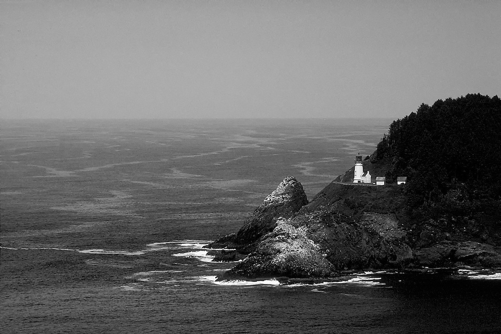 Black and White Waterscape image of the Calm Pacific Ocean and a Large rock formation with a Lighthouse on the Pacific Northwest Coastline. Heceta Lighthouse or 6-B is located in a cove at the mouth of Cape Creek which includes Devils Elbow State Park. Long shot from the highway.