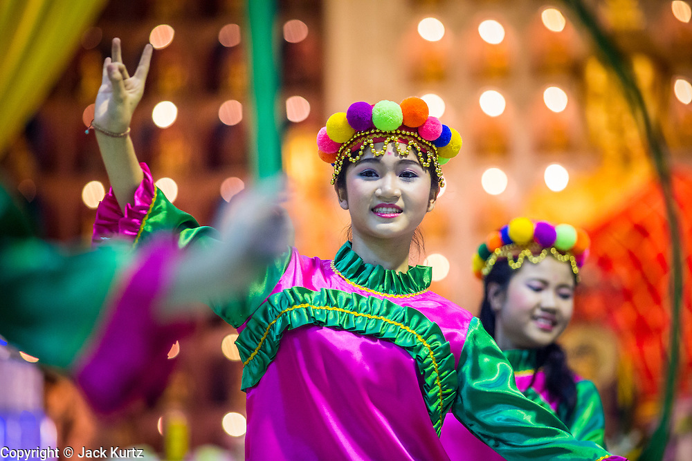 23 OCTOBER 2012 - HAT YAI, SONGKHLA, THAILAND: Girls perform a traditional dance on the last day of the Vegetarian Festival at Wat Ta Won Vararum, a Chinese Buddhist temple in Hat Yai. The Vegetarian Festival is celebrated in Thai-Chinese communities throughout Thailand. It is the Thai Buddhist version of the The Nine Emperor Gods Festival, a nine-day Taoist celebration celebrated in the 9th lunar month of the Chinese calendar. For nine days, those who are participating in the festival dress all in white and abstain from eating meat, poultry, seafood, and dairy products. Vendors and proprietors of restaurants indicate that vegetarian food is for sale at their establishments by putting a yellow flag out with Thai characters for meatless written on it in red.   PHOTO BY JACK KURTZ