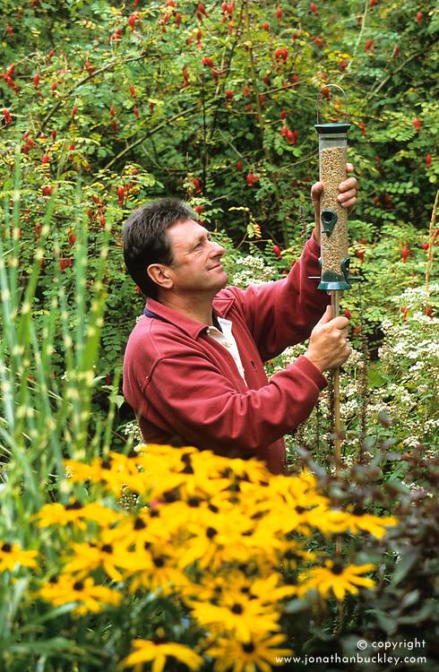 Alan Titchmarsh putting up a bird feeder