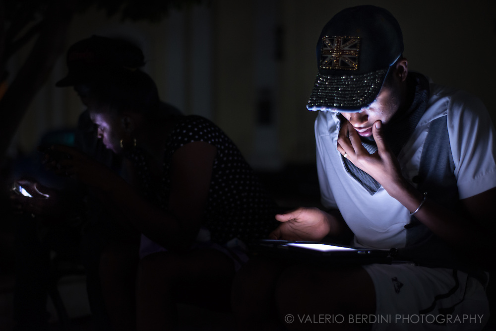 A young man in a union jack baseball cap, lit up by the glow of his  tablet, sits in Plaza Carillo in Trinidad de Cuba on Christmas day night 2015. Cuban parks, usually poorly illuminated at night, in the last few months have been glowing by the flickering lights of several electronic device. These people were aware of the photographer, but they continued their activity. This photo was not staged.