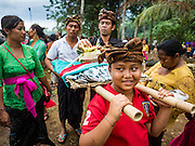 13 JULY 2016 - UBUD, BALI, INDONESIA:  A boy carries the burned bones of a member of the community after the mass cremation Wednesday. Local people in Ubud exhumed the remains of family members and burned their remains in a mass cremation ceremony Wednesday. Almost 100 people will be cremated and laid to rest in the largest mass cremation in Bali in years this week. Most of the people on Bali are Hindus. Traditional cremations in Bali are very expensive, so communities usually hold one mass cremation approximately every five years. The cremation in Ubud will conclude Saturday, with a large community ceremony.     PHOTO BY JACK KURTZ