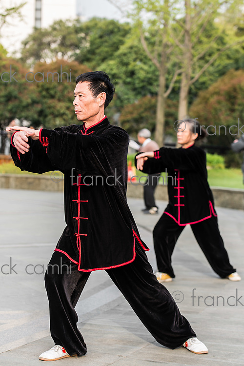 Shanghai, China - April 7, 2013: people exercising tai chi with traditional costume in gucheng park in the city of Shanghai in China on april 7th, 2013
