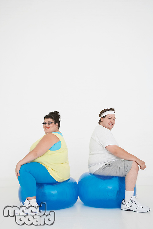 Overweight man and woman sitting back to back on exercise balls portrait