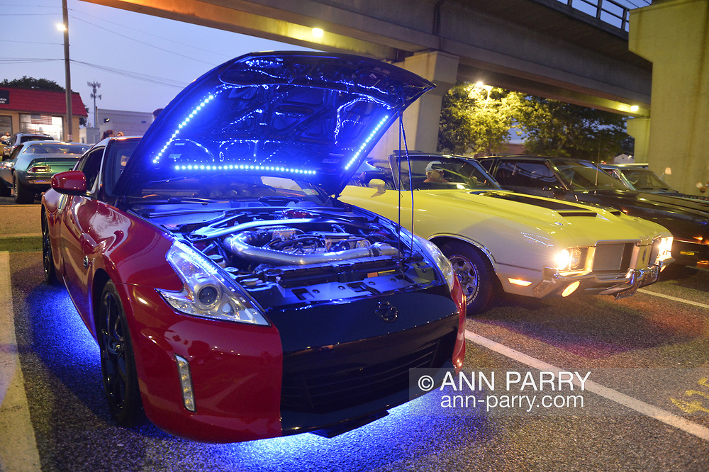 Bellmore, New York, USA. August 24, 2018. Red 2014 Nissan 370Z, with open hood showing engine area lit blue, is parked under elevated tracks of LIRR train station during Bellmore Friday Night Car Show. Owner sits nearby in purple portable chair.