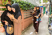 "08 AUGUST 2013 - BANGKOK, THAILAND: Thai Muslim girls look at their smart phone in alley next to Haroon Mosque in Bangkok after Eid al-Fitr services. Eid al-Fitr is the ""festival of breaking of the fast,"" it's also called the Lesser Eid. It's an important religious holiday celebrated by Muslims worldwide that marks the end of Ramadan, the Islamic holy month of fasting. The religious Eid is a single day and Muslims are not permitted to fast that day. The holiday celebrates the conclusion of the 29 or 30 days of dawn-to-sunset fasting during the entire month of Ramadan. This is a day when Muslims around the world show a common goal of unity. The date for the start of any lunar Hijri month varies based on the observation of new moon by local religious authorities, so the exact day of celebration varies by locality.      PHOTO BY JACK KURTZ"
