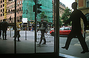 Human office window pedestrian figures echo real passers-by in a street in central Frankfurt.