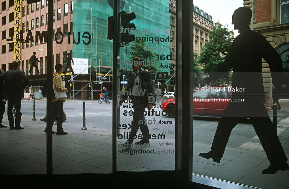 Human office window pedestrian figures echo real passers-by in a street in central Frankfurt.
