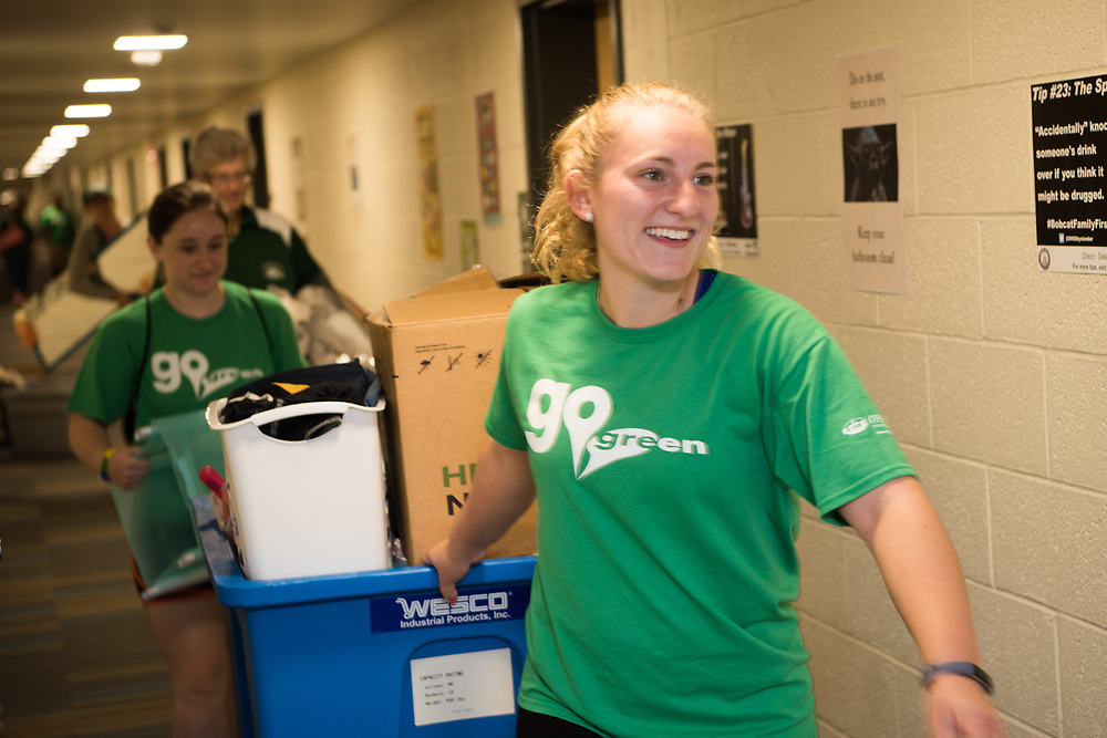 Go Green volunteer Katherine Boehlefeld helps first year students move into their residence hall Thursday morning. Photo by Ben Siegel