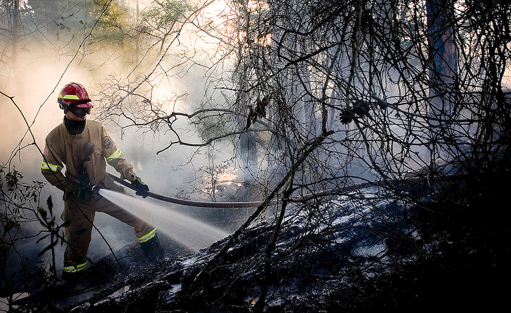 Chapel Hill Fire Fighter Justin Stowe age 20 sprays foam on a fallen tree at a brush fire in northern Smith County on Wednesday, February 18, 2009.  Seven area fire department respond the fire that burned over 50 acres.  Photos By Tom Turner