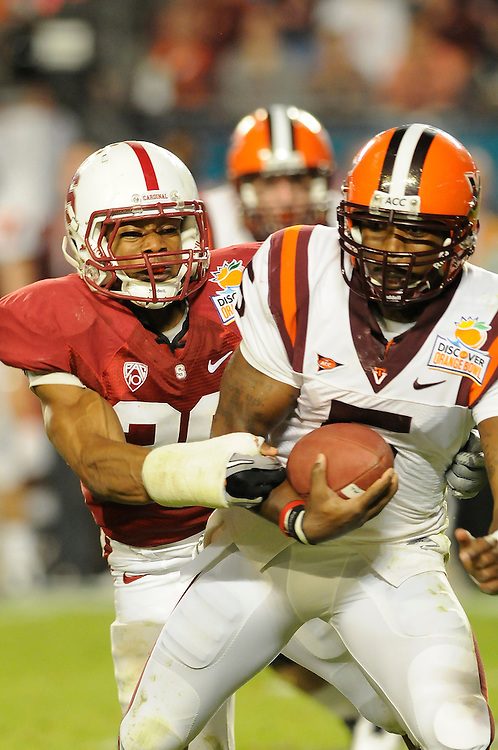 January 3, 2011: Tyrod Taylor of the Virginia Tech Hokies is pressured by Delano Howell of the Stanford Cardinal during the NCAA football game between the Stanford Cardinal and the Virginia Tech Hokies at the 2011 Orange Bowl in Miami Gardens, Florida. Stanford defeated Virginia Tech 40-12.
