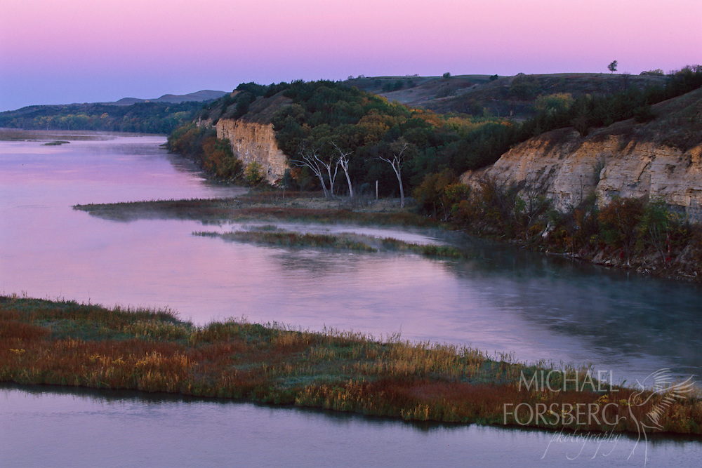 Pastel blue and violet twilight overlays the vibrant reds and yellows of fall along the Missouri River.  Border between South Dakota and Nebraska.