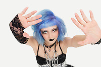 Portrait of young female punk making a stop gesture over gray background