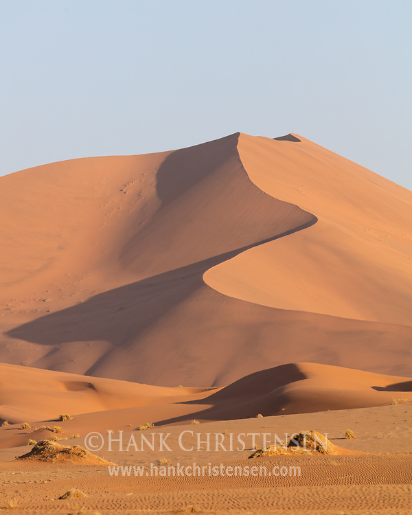 A massive sand dune glows red orange in the setting sun, Namib-Naukluft National Park, Namibia.