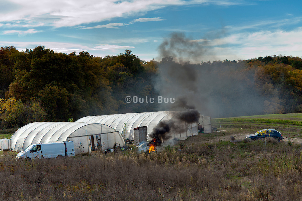 dark black smoke from waste burning by greenhouse France