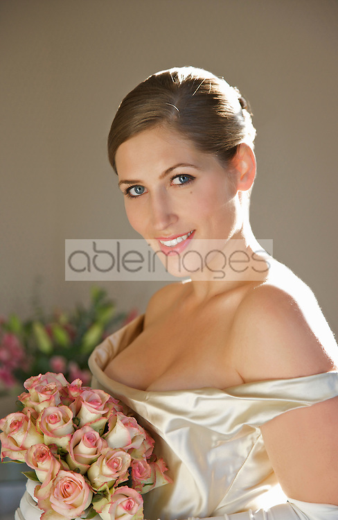 Close up of a smiling bride in a white wedding gown holding a bouquet of roses