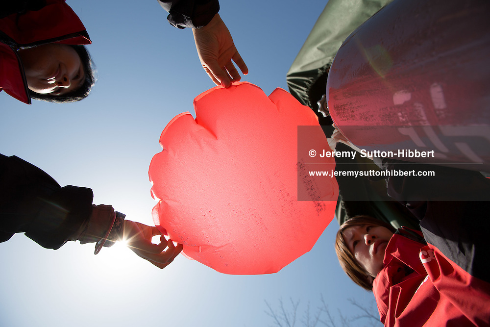Greenpeace staff and volunteers stamp contact and numbering information onto red paper balloons, which are then filled with helium and released, in a bid to track wind dispersal patterns around the Oi nuclear plant, near Obama town, Fukui prefecture, Japan, on Wednesday 29th March 2012.