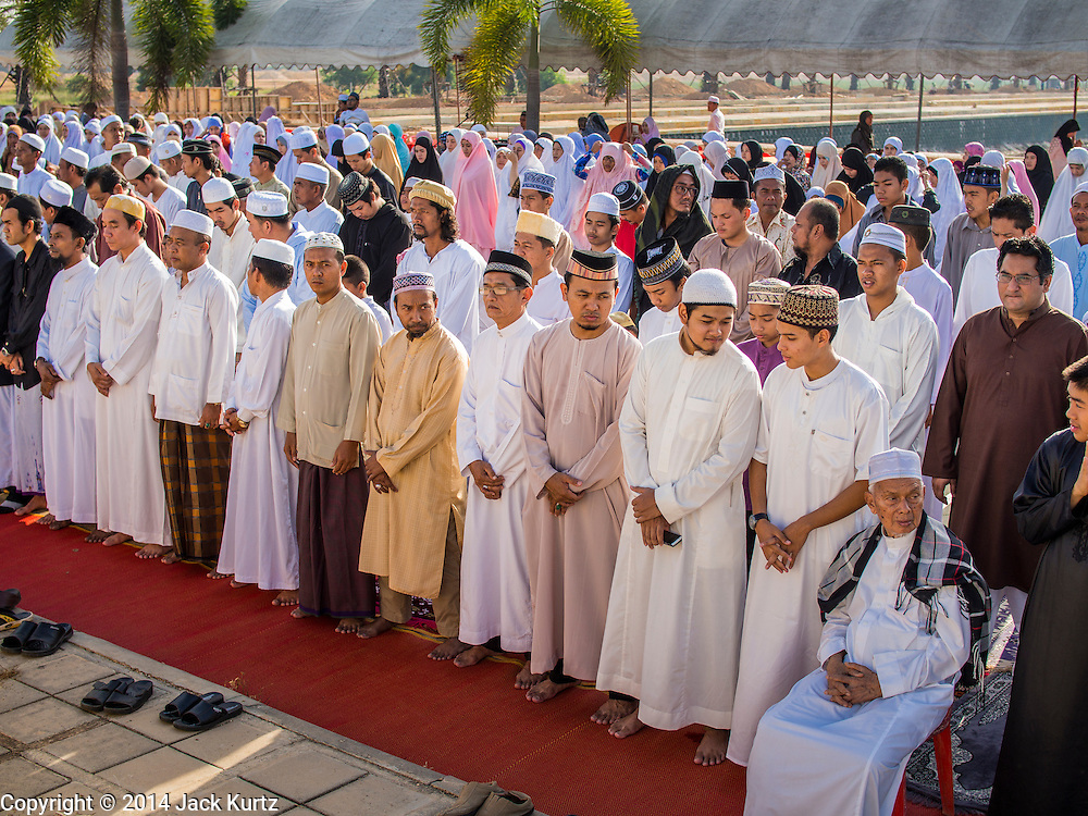 28 JULY 2014 - KHLONG HAE, SONGKHLA, THAILAND: Men pray during Eid services at Songkhla Central Mosque in Songkhla province of Thailand. Eid al-Fitr is also called Feast of Breaking the Fast, the Sugar Feast, Bayram (Bajram), the Sweet Festival and the Lesser Eid, is an important Muslim holiday that marks the end of Ramadan, the Islamic holy month of fasting.   PHOTO BY JACK KURTZ