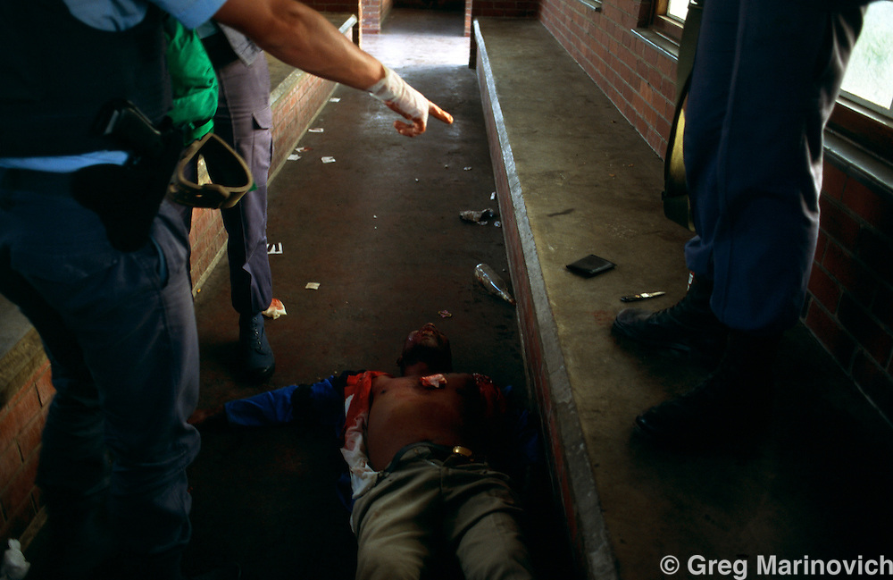 Police look at a man killed in violence following a political rally in Umlazi, KwaZulu Natal, South Africa. 1994