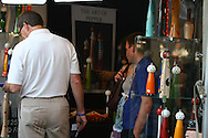Shoppers admire artistic wooden pepper grinders for sale in artist's booth at the St. Louis Art Fair in Clayton, Missouri.