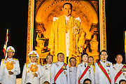 YINGLUCK SHINAWATRA the Prime Minister of Thailand, and ANUSORN AMORNCHAT, her husband, (right) on stage the celebration of the birthday of the King in Bangkok. Thais observed the 86th birthday of Bhumibol Adulyadej, the King of Thailand, their revered King on Thursday. They held candlelight services throughout the country. The political protests that have gripped Bangkok were on hold for the day, although protestors did hold their own observances of the holiday. Thousands of people attended the government celebration of the day on Sanam Luang, the large public space next to the Grand Palace in Bangkok.