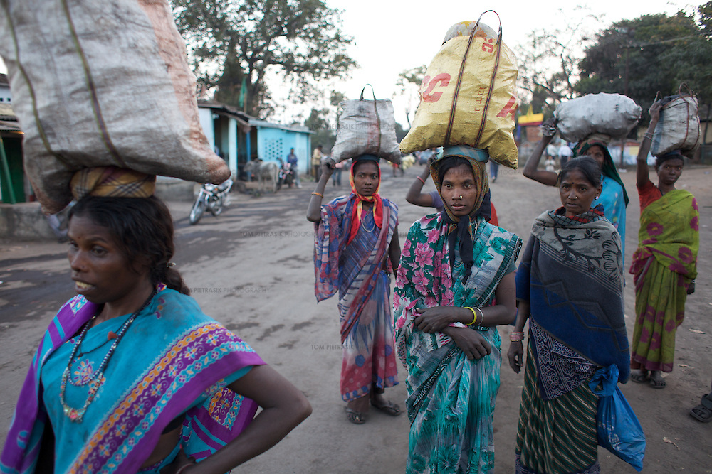 Indigenous Adivasi women wait for taxis to take them home with coal they have illegally collected around the site of the Parej open cast mine in Hazaribagh district. The Indian state of Jharkhand boasts huge mineral deposits, including coal. Yet it is home to some of the poorest people in India. As mining companies have moved in, so Adivasi communities have been forced from their land. Despite their sacrifice, these people remain marginalised and poor. Few of them find jobs in the big mines. And with few alternative employment opportunities, many eke out a living by scavenging coal from the edges of mines. ..Photo: Tom Pietrasik.Jharkhand, India.January 29th 2010