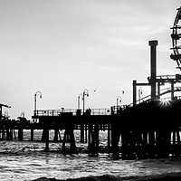 Santa Monica Pier black and white panoramic picture. Santa Monica Pier is a landmark located in Los Angeles county that has an amusement park with a ferris wheel, roller coaster, restaurants, and other attractions. Image Copyright © 2012 Paul Velgos with all rights reserved.