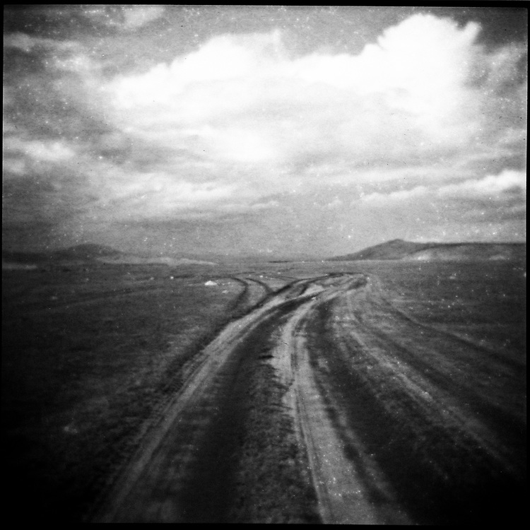 A black and white image of  a long, desolate road in the steppes of northern Mongolia.