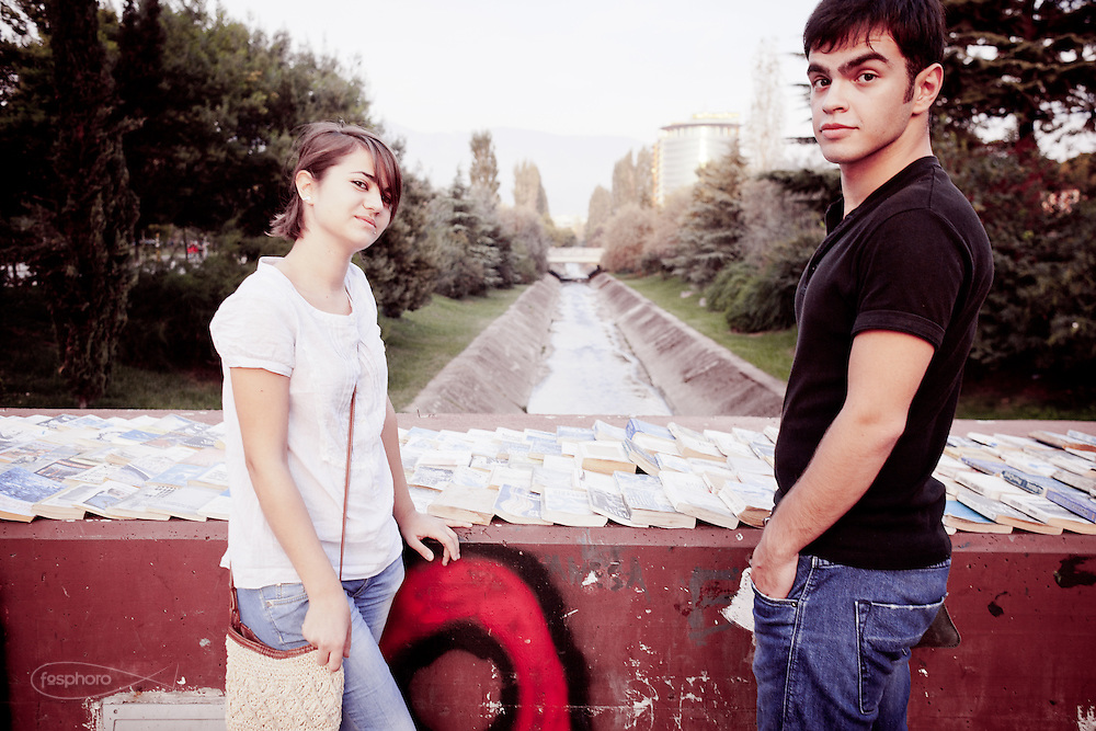 Sara (20) and Ohana (20), born 1991, both classmates and ex-call center operators. Student in Economics and Finance her, student in Engineering him. Both would like to complete their studies abroad, but not in Italy. Used books for sale on a bridge over the Lana river.