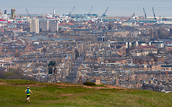 Edinburgh, Scotland, UK. 5 April, 2020. On the second Sunday of the coronavirus lockdown in the UK the public are outside taking their daily exercise. A man running on Salisbury Crags in Holyrood Park with Leith in distance. Iain Masterton/Alamy Live News