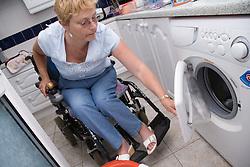 Woman wheelchair user loading the washing machine,