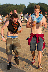 © Licensed to London News Pictures . 21/07/2013 . Suffolk , UK . Two men carrying drinks laugh as one spills some on the ground . The Latitude music and culture festival in Henham Park , Southwold . Photo credit : Joel Goodman/LNP