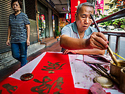 11 JANUARY 2019 - BANGKOK, THAILAND: A woman walks past a calligrapher writing Chinese New Year greetings on a table he set up in Bangkok's Chinatown. Calligraphers set up tables throughout Chinatown in the weeks leading up to Chinese New Year. About 14% of Thais are of Chinese ancestory and Lunar New Year is widely celebrated in Thailand. Chinese New Year celebrations in Bangkok start on February 4, 2019. The coming year will be the Year of the Pig in the Chinese zodiac.      PHOTO BY JACK KURTZ