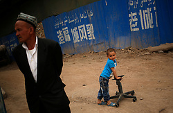 A picture made available on 27 May 2013 of a man and boy of the Uighur ethnic group in the old town of Kashgar where it is being renovated in Kashgar, the western edge of China's Xinjiang Uighur Autonomous Region, China 25 May 2013. Kashgar old town's historic labyrinth of earthen mud houses are rapidly being demolished and revamped in a massive government plan to transform the city since 2009. The Chinese government, citing unsafe structures and non-compliance with fire and earthquake safety regulations, has razed and rebuilt more than two thirds of the old city by 2012, relocating thousands of its mainly Uighur ethnic minority residents. Uighurs make up about the majority of the 3.9 million people living in the restive region of Kashgar where the north and south silk road met. Tensions between the Uighurs and Han Chinese have been high as they complain of cultural and religious repression and claim that ethnic Chinese migrants enjoy the main benefits of development in the oil-rich but economically backward region.