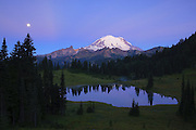 The full moon sets near Mount Rainier and Tipsoo Lake, located near Chinook Pass, Washington.