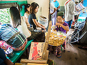 05 JUNE 2014 - YANGON, YANGON REGION, MYANMAR: A snack vendor on the Yangon Circular Train. The Yangon Circular Train is a commuter train that circles Yangon, Myanmar (Rangoon, Burma). The train is 45 kilometers long, makes 38 stops and takes about three hours to make a loop of the city.     PHOTO BY JACK KURTZ