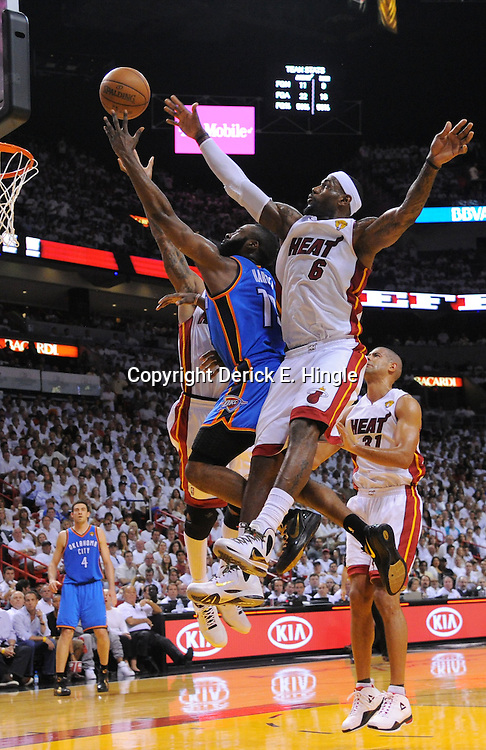 Jun 17, 2012; Miam, FL, USA; Oklahoma City Thunder guard James Harden (13) drives against Miami Heat power forward Udonis Haslem (40) and small forward LeBron James (6) during the first quarter in game three in the 2012 NBA Finals at the American Airlines Arena. Mandatory Credit: Derick E. Hingle-US PRESSWIRE