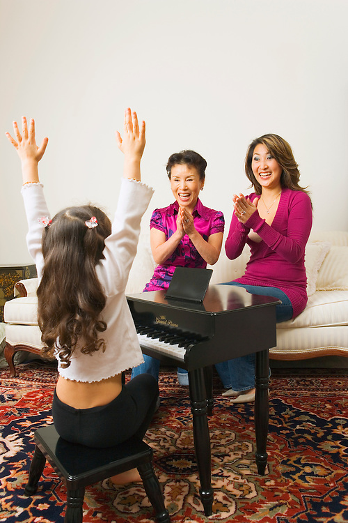 Mother and grandmother encouraging young girl performing on toy piano.
