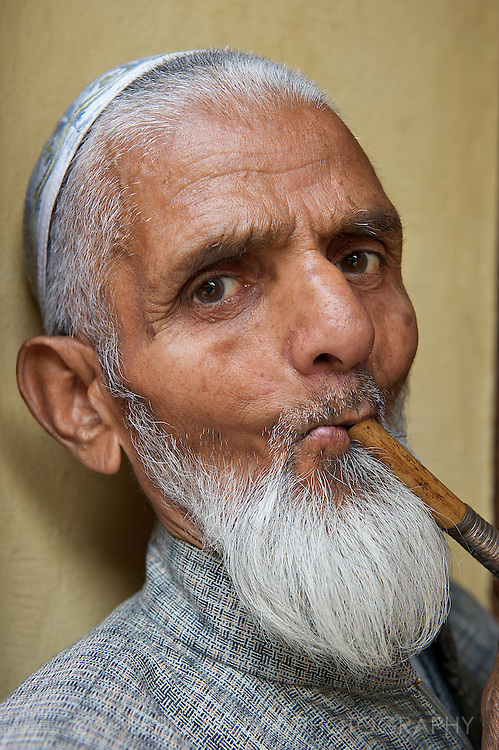 An old man smokes tobacco from a traditional Kashmiri wooden pipe.